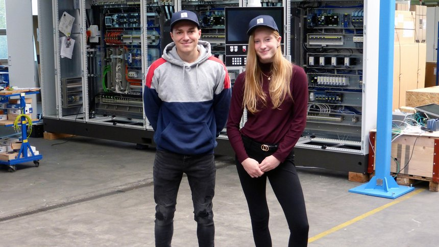 Two Kurre trainees in the production site are dressed in new company caps.