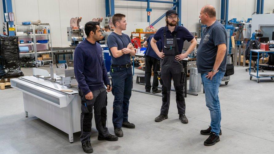 Jugendliche im Gespräch mit Ausbilder in einer Produktionshalle