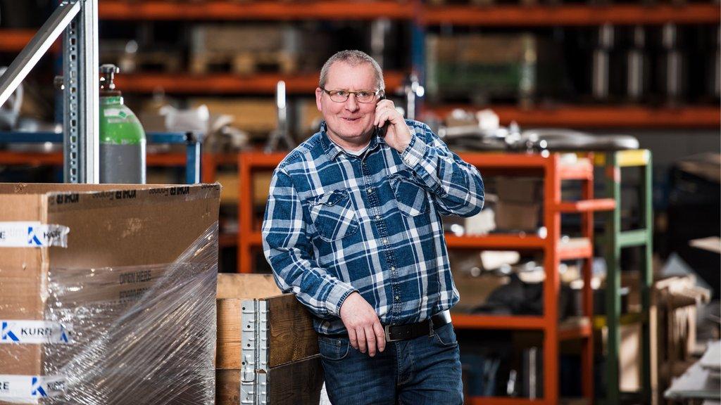 Mann telefoniert in einer Produktionshalle