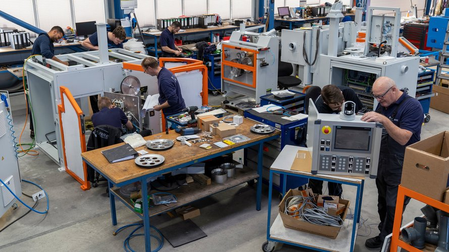 Mehrere Auszubildende und Gesellen arbeiten an einer Kabelmaschine