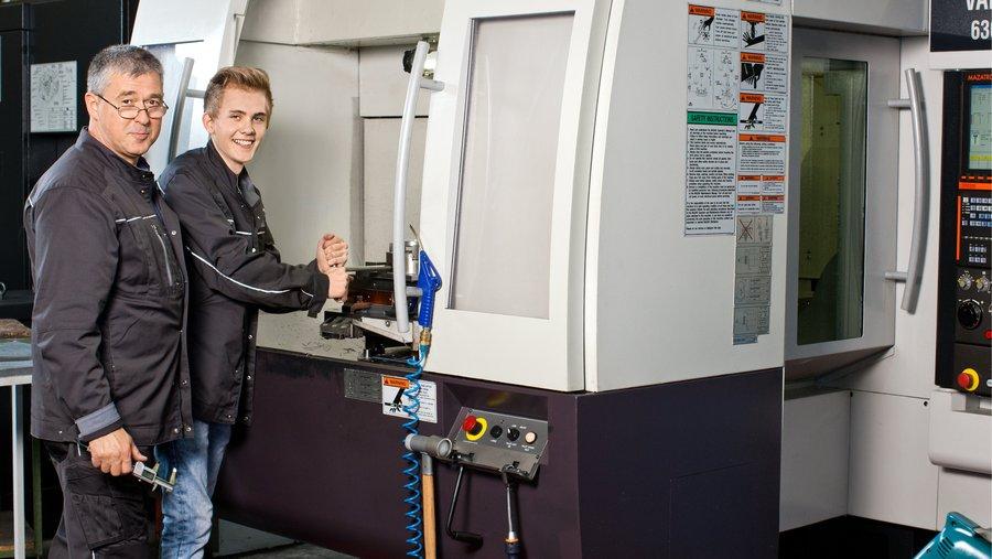 Ausbilder und Jugendlicher arbeiten gemeinsame an einem CNC-Maschine.