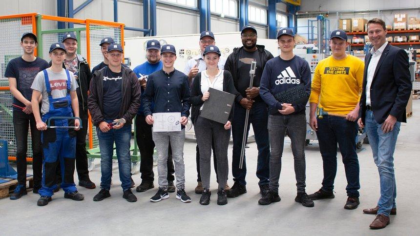 12 Azubis von Kurre stehen in der Produktionshalle und tragen neuen Firmencappys. Jeder hat ein Werkzeug seines Berufes in der Hand.