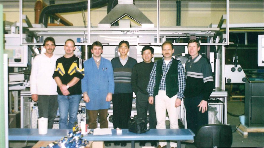 Older photo of employees in front of a machine.