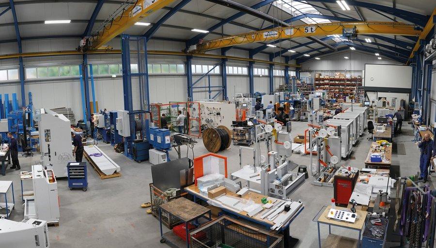 Moderne Produktionshalle, in der Maschinen aus den Bereichen Draht- und Kabelverarbeitung zusammengebaut werden.