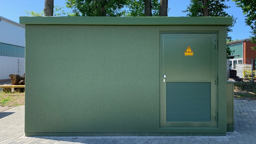 Große grüne Transformatorstation (Elektro) auf einem Firmengelände.