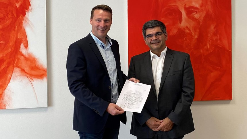 Firmeninhaber Stefan Plaggenborg und der österreichische Mitarbeiter Robert Pinter zeigen einen Vertrag.