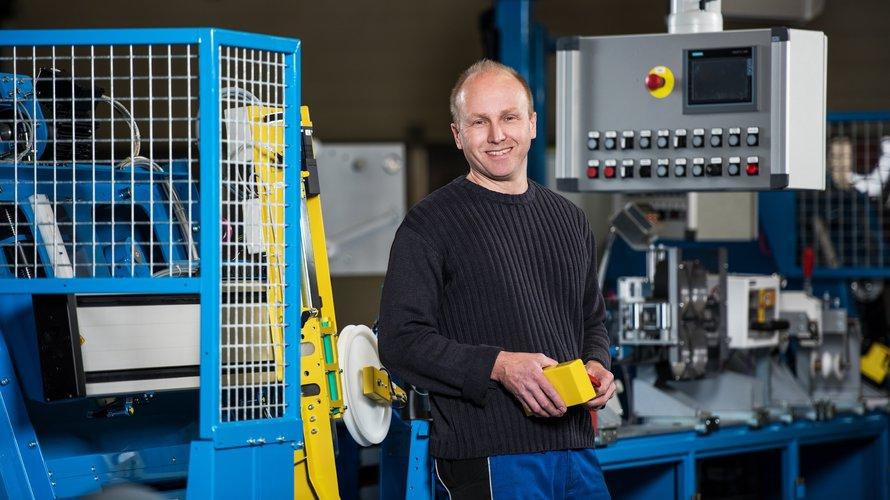 Mann arbeitet in einer Montagehalle