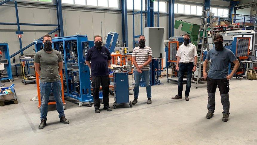 5 Männer stehen mit großen Abständen in einer Maschinenproduktionshalle.