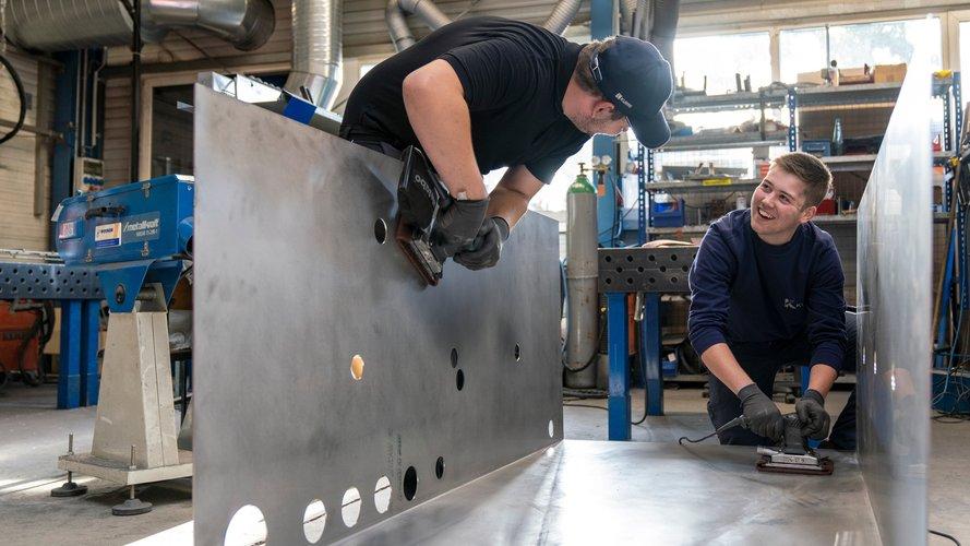 Zwei junge Männer arbeiten mit Schleifmaschinen